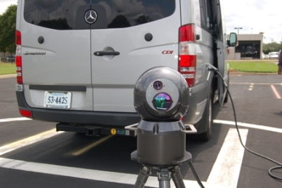 Photograph of the IRIS unit standing on a tripod behind the truck